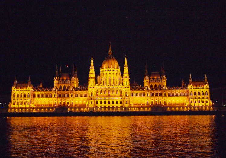 The Hungarian Parliament building, overlooking the Danube River at night.